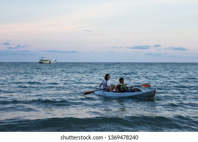 TRAT, THAILAND. APR 11, 2017: Couple tourist kayaking over the sea wave surface that reflected with blue and purple sky color in the evening in Koh Mak Island at Trat, Thailand.