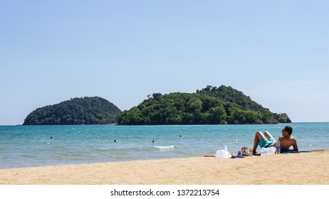 TRAT, THAILAND. APR 11, 2017: Mountain island over the sea with tourist lay down on the beach on the right side with bright sky in background in the afternoon at Koh Mak Island in Trat, Thailand.
