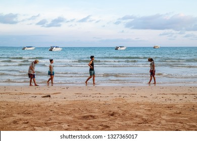 TRAT, THAILAND. APR 9, 2017: Diversity of people walking on the beach and looking to the sea with speed boats and bright sky in the background at Koh Mak Island in Trat, Thailand.
