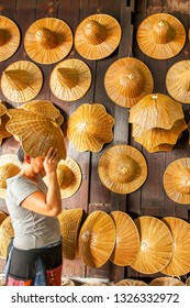 Trat, Thailand - MARCH 10, 2011: An asian woman choosing a farmer's weaving hat in souvenir shop, lots of weaving hat made of palm leaves, local product of Ban Nam Chiew. Trat.