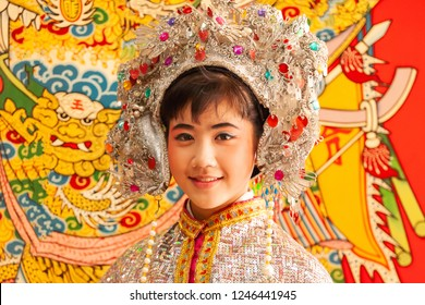 Trat, Thailand - MARCH 11, 2011: Adorable face of a chinese opera actress in beautiful traditional costume, smiling at camera, colorful of traditional chinese painting on chinese temple wall. Trat.