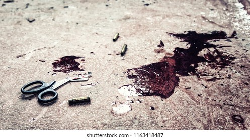 Trauma shears or bandage scissors lying on floor with stains of human blood around. Blood loss and bleeding stop, emergency medical aid for gunshot wounds, tactical combat casualty care on battlefield