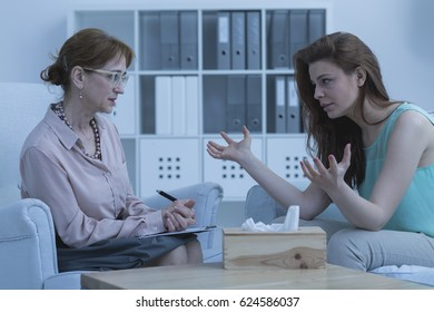 Traumatized woman discussing her problems with psychologist