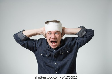Traumatized young guy with bandage on his head putting hands on wound. Image related with treatment of the wounds
