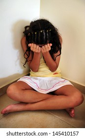 Traumatized young woman sit on the floor in the corner of here home - concept photo of  of sexual assault