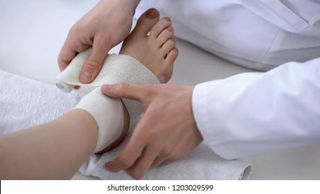 Traumatologist applying bandage to sprained ankle, workout injury, leg closeup