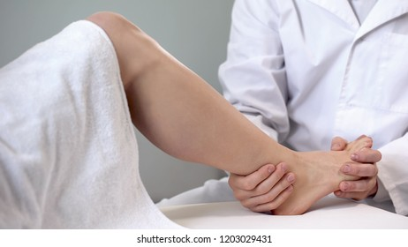 Traumatologist moving patient ankle, assessing severity of injury, closeup