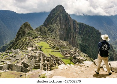 Travaler at Site of the Lost Inca City of Machu Picchu near Cusco, Peru. Machu Picchu is a Peruvian Historical Sanctuary and a UNESCO World Heritage Site. One of the New Seven Wonders of the World.