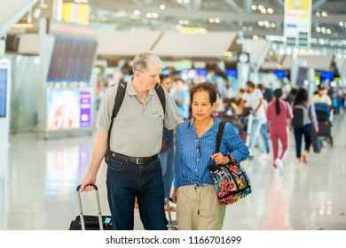 Travel abroad. Portrait of Senior couple  are standing together at international airport and airport terminal blurred crowd of travelling people on background. Copy space