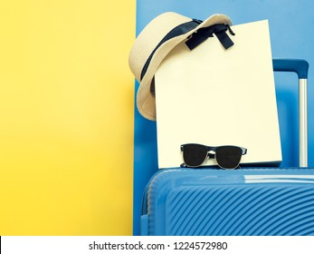 travel accessories for christmas and new year event concept from colorful luggage or suitcase with hat on travel and shopping bag with blue and yellow pastel background