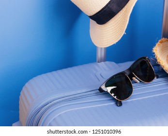 travel accessories for christmas and new year event concept from colorful luggage or suitcase with travel hat and sunglasses with blue and yellow pastel background