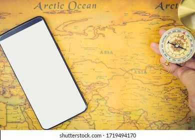 Travel accessories concepts : It's time to go to travel around the world - The image of a world map with essentials accessories - smart phone and compass. Vintage tone style. Top view picture.