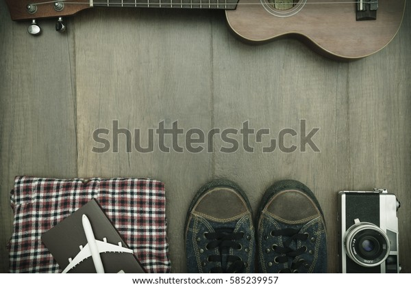 Travel accessories costumes. Passports, luggage, hat,guitar, travel maps,camera prepared for the trip place on brown wood texture,retro tone with vignette