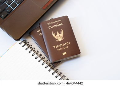 Travel accessories costumes. Passports Thailand, Preparation for travel, Notebook pen on top and laptop or computer for vacation time, soft focus.