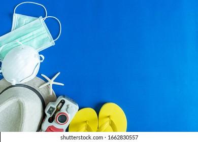 Reisezubehör, Hut, Kamera, Hausschuhe und Seesterne mit Maske auf blauem Hintergrund mit freiem Platz. Sicherheitsausflug vom Covid-19-Viruskonzept.