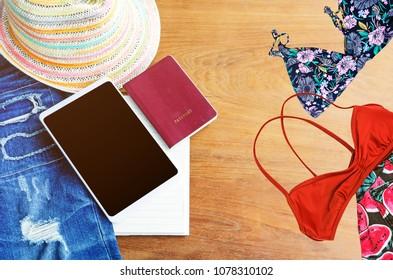 Travel accessories. Hat, smartphone,  torn jean, book, passport and bikini on wood table.