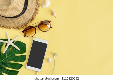 Travel accessories items with smart phone on yellow background, Summer vacation concept