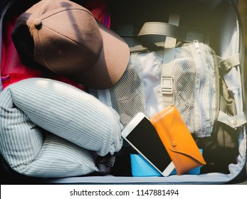 travel and accessories minimal flat lay concept from top view phone ,hat and other necessary item prepare in luggage