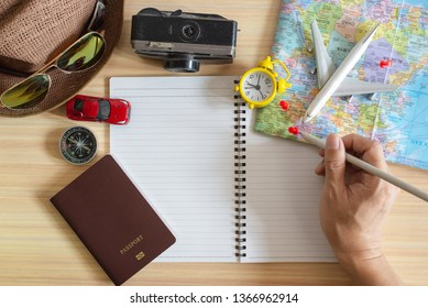 Travel accessories set on wooden background:passport,compass,notebook,clock hat, map, camera,carmodel,airplane moddel and sunglasses. Top view point.Young man planning vacation trip with map.
