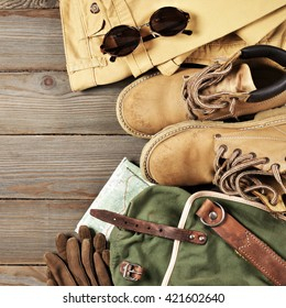 Travel accessories set on wooden background: old hiking leather boots, pants, backpack, map, gloves and sunglasses. Top view point.