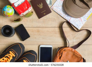 Travel accessories set on wooden background:phone,passport shoes, cap, bag leather, map, camera and sunglasses. Top view point.