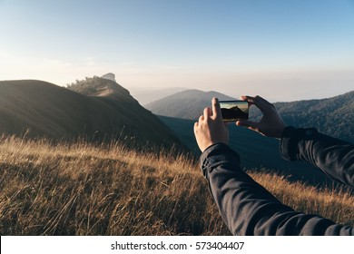 Travel accessories for taking photo by smart phone,Hand holding Smart phone and take photograph,Camera for Travel accessories,Film look color tone and selective focus on hand.Day light in the morning.