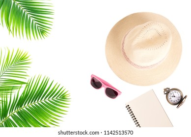 Travel accessories with tropical palm leaves,sunglasses,notebook,pocket watch,and straw hat on white bacground