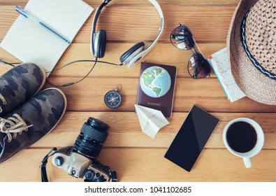 Travel accessories,trip vacation, tourism mock up of smartphone,road map,compass,camera,hat,shoes,sunglasses,passport,paper plane,headphones,coffee cup, on wooden table.
