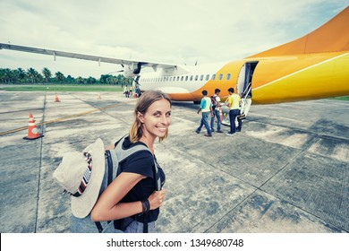 Travel and active lifestyle concept. Departure. Young woman boarding on aircraft  at an airfield.