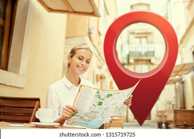 Travel and active lifestyle concept. Young traveller woman sitting in old town cafe terrace and planning trip with map with 3d red location pin GPS pointer on the background.