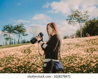 travel and adventure concept from beautiful black long hair photographer asian girl with her camera travel and take photo at flower field with soft focus background