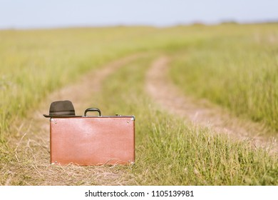 Travel and adventure concept. Vintage brown suitcase and hat on the road in the green field.