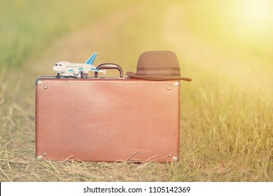 Travel and adventure concept. Vintage brown suitcase and hat with toy airplane near the road in the green field.