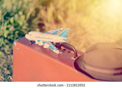 Travel and adventure concept. Vintage brown suitcase and hat with toy airplane in the green field. Toned