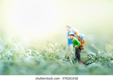 Travel and Adventure concepts. Group of travelers miniature mini figures with backpack stand and walking on meadow