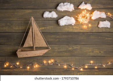 Travel and adventure creative concept - toy boat on a wooden background with cotton clouds. Christmas lights as a sea waves
