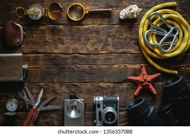 Travel or adventure equipment and accessories flat lay background with copy space. Photo camera, flashlight, multitool knife, rope, carbines, binoculars, compass, wallet and pocket watch on table.
