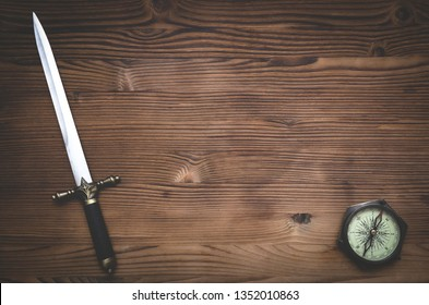 Travel or adventure flat lay background with copy space. Adventurer table. Compass and a dagger knife on the table.