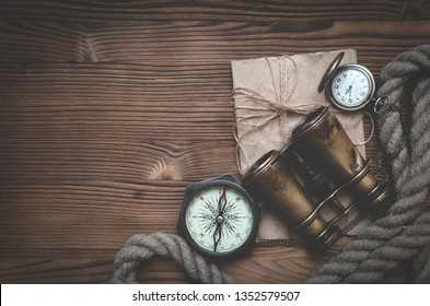Travel or adventure flat lay background with copy space. Adventurer table. Binoculars, parchment, moorings, compass and pocket watch on the table.