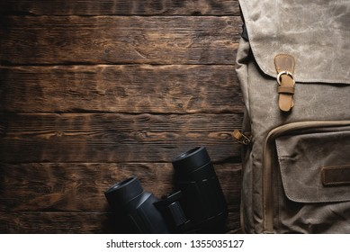 Travel or adventure flat lay background with copy space. A backpack and a binoculars on a brown wooden table.