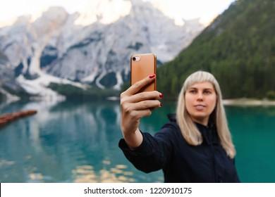 Travel and adventure. Travel hiker makes selfie photo on smartphone on beautiful landscape, Dolomites Mountaines. Braies Lake (Lago di Braies), hiking on alpine lake, Alps, Dolomites, Italy, Europe