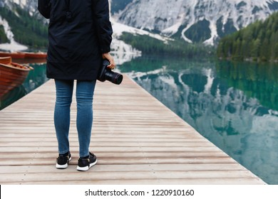 Travel and adventure. Hiker, photographer with camera on beautiful landscape background, Dolomites Mountaines. Braies Lake (Lago di Braies), hiking on alpine lake, Alps, Dolomites, Italy, Europe