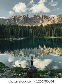 Travel and adventure. Young traveler girl with backpack and hat standing near mountains alpine lake, Alps, Dolomites, Italy, Europe.