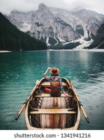 Travel and adventure. Young traveler girl with backpack and hat in the boat on a mountains alpine lake, Alps, Dolomites, Italy, Europe.