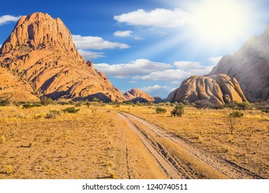 Travel to Africa. Picturesque cliffs in the desert Namib. The morning hot sun in the African desert. Rocks in the Spitskoppe desert. The concept of active, extreme and photo-tourism