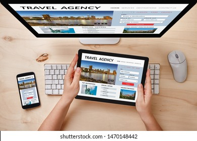 Travel agency concept on computer, tablet and smartphone screen over wooden table. Top view of responsive devices.
