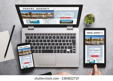 Travel agency concept on laptop, tablet and smartphone screen over gray table. Flat lay