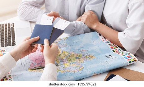 Travel agency. Couple getting passports and tickets, closeup