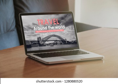 Travel agency website in a laptop screen over a wooden table.