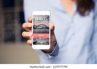 Travel agency website in a mobile phone screen while woman holds the device.